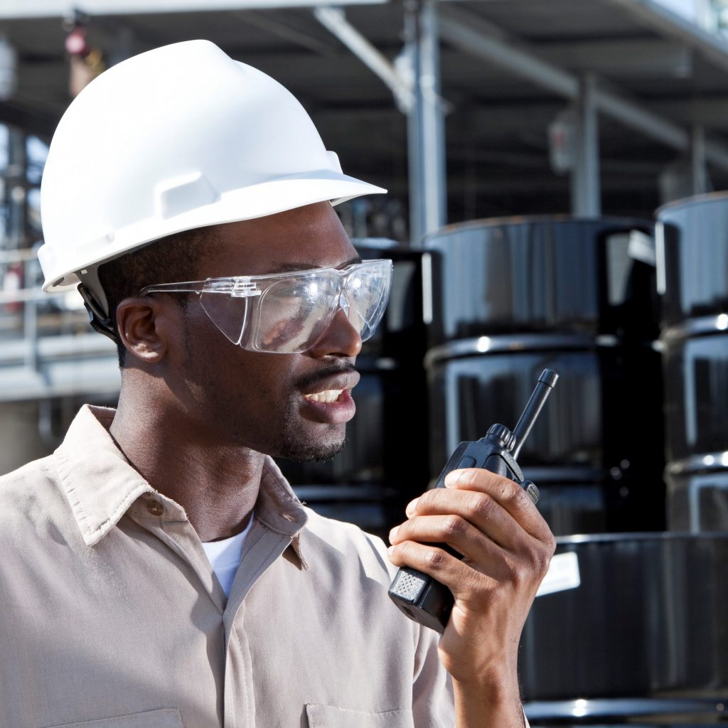Young African American worker speaking into walkie-talkie, at chemical plant