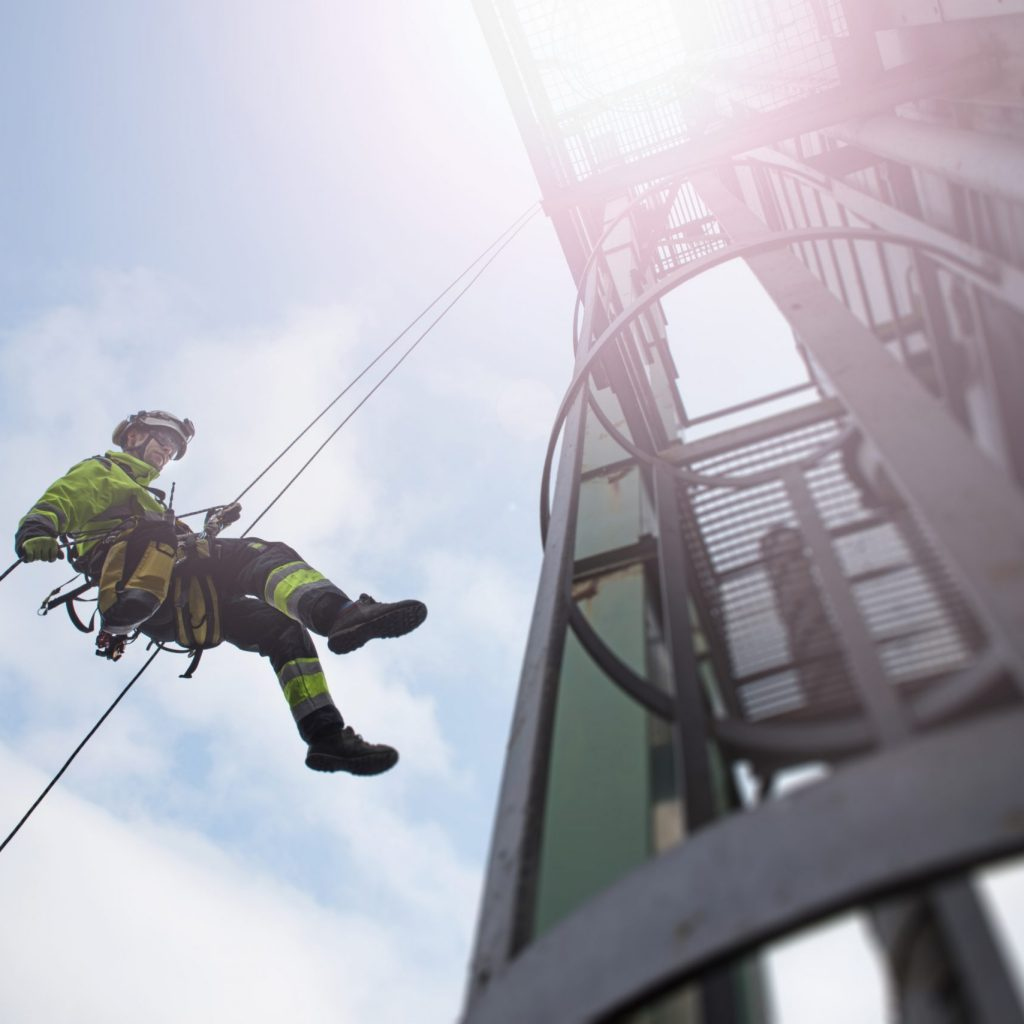 View from bottom on rope access technicians abseil from tower high up with sun behind