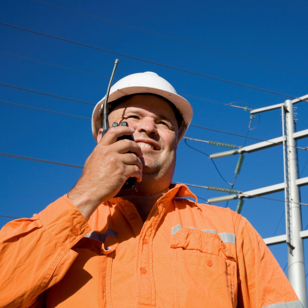 A worker on radio with power lines in background. Could be an Electrician or other Electrical worker in an engineering field. A professional attitude displayed in an industrial environment.
