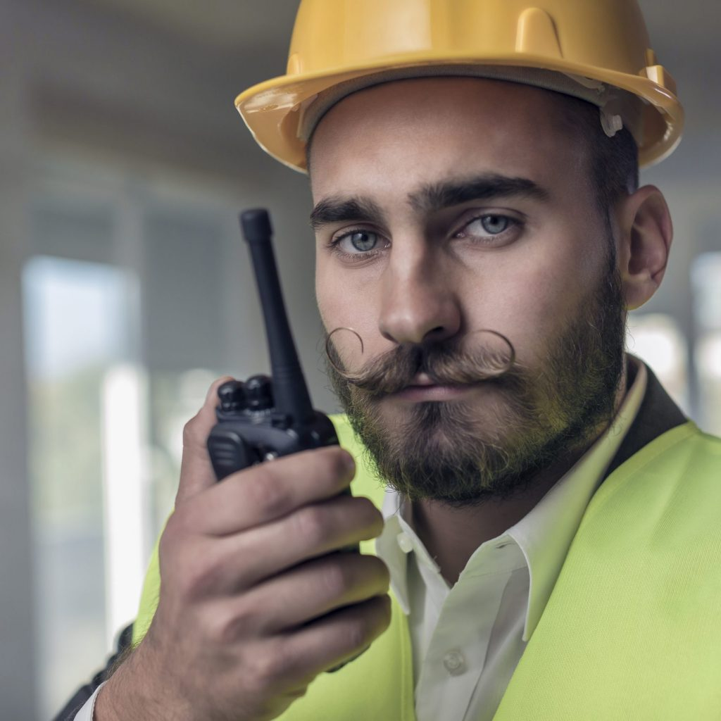 Young hipster constructor using a two way radio at the construction site.