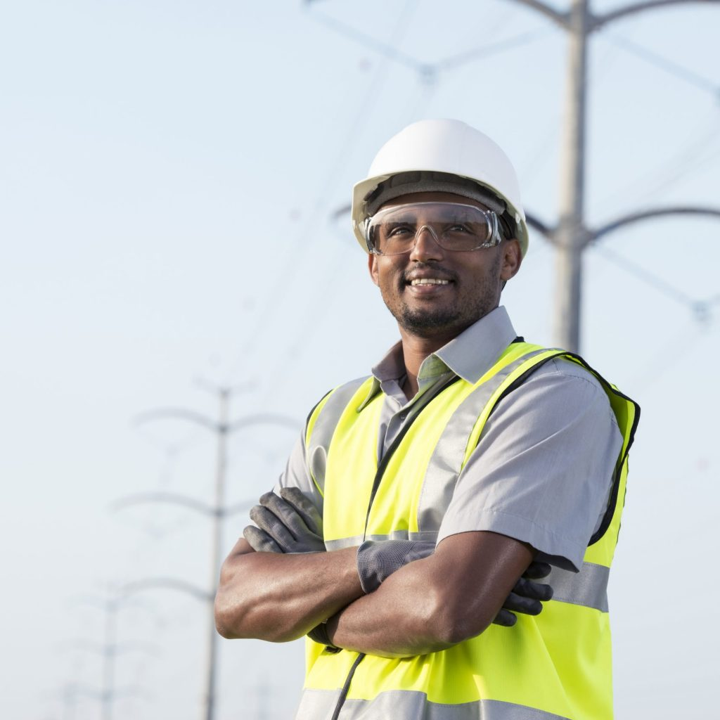Portrait of manual worker in Personal protective equipment (PPE) standing under high voltage transmission lines against tubular transmission towers.