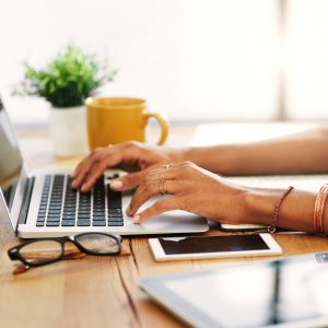 Cropped shot of an unrecognizable businesswoman sitting alone and typing on her laptop during the day at home