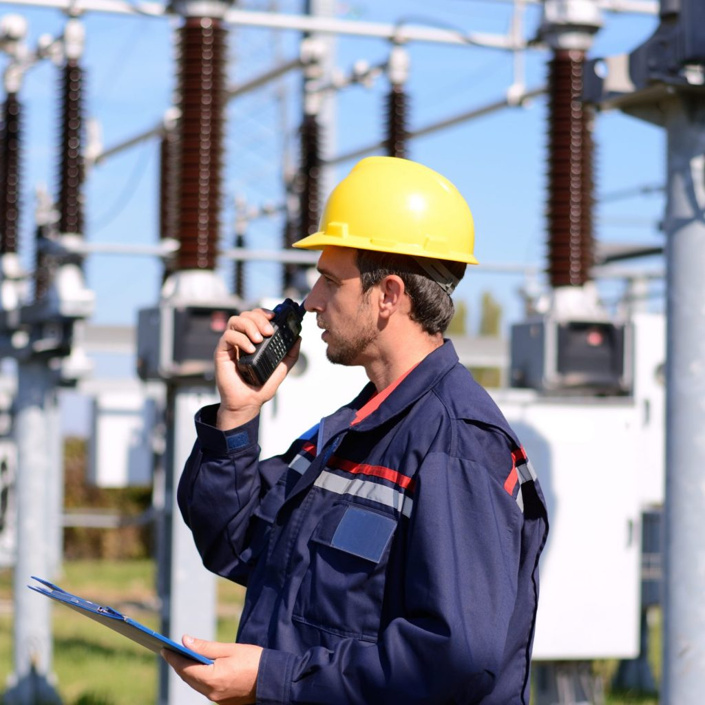 Electrician working in power plant. Man at work with Walkie Talkie and ring binder in his hand.