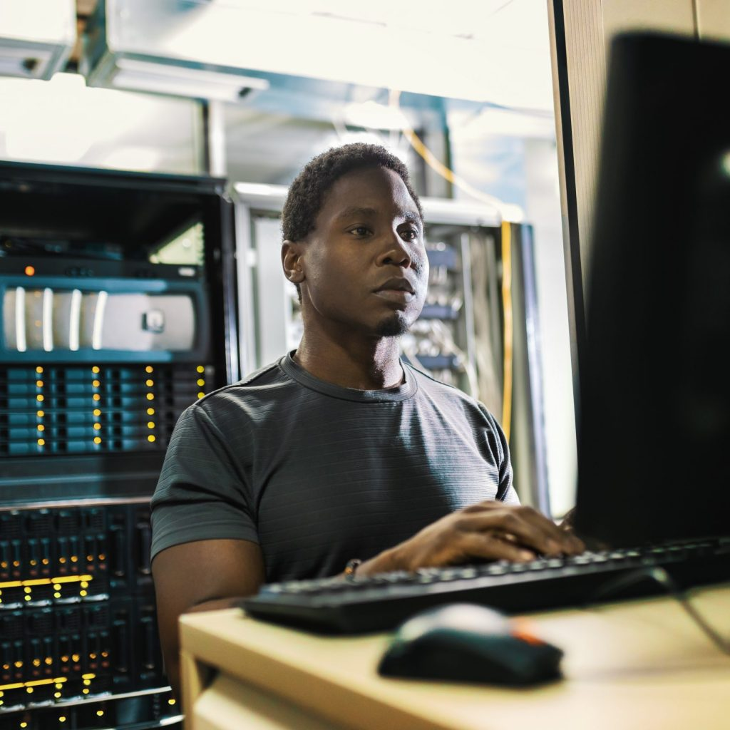 System administration, man is working in data center with laptop