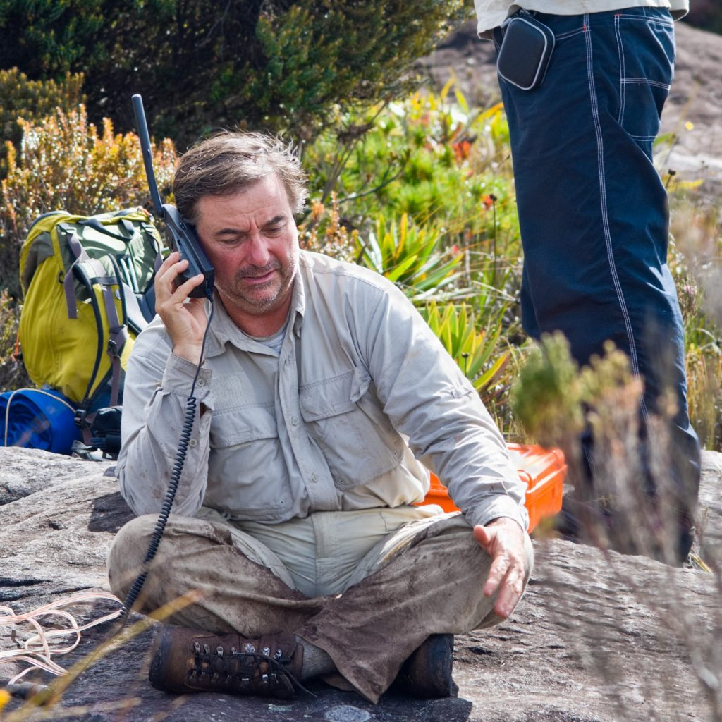 Expeditionary with a satellite portable phone at Auyan Tepuy, Venezuela