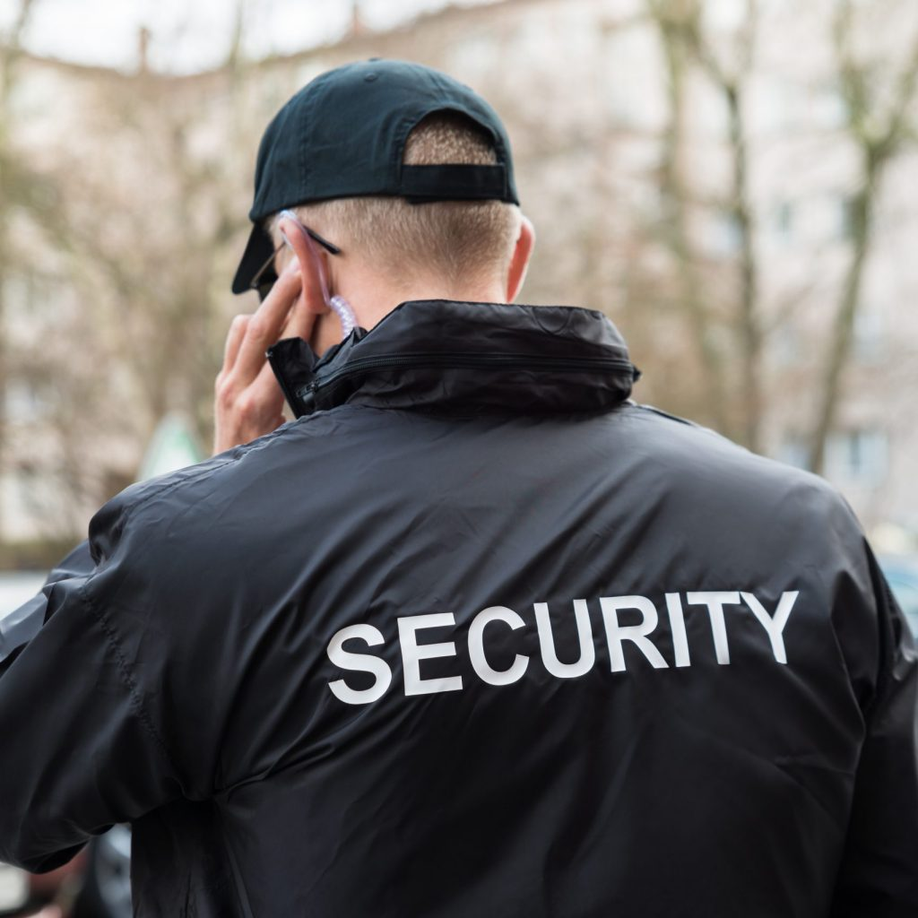 Security Guard In Black Uniform Listening With Earpiece