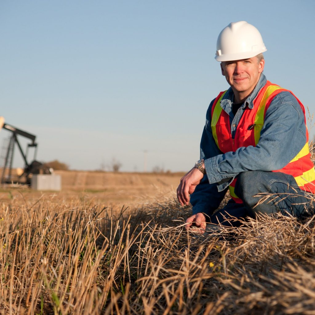 Oil worker engineer in safety gear inspects the soil near an oil well pumpjack.  Alberta Canada in the fall.
