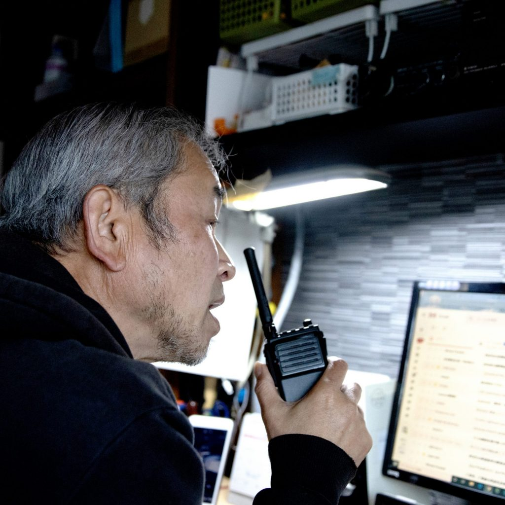 A man giving instructions by radio while looking at a personal computer screen