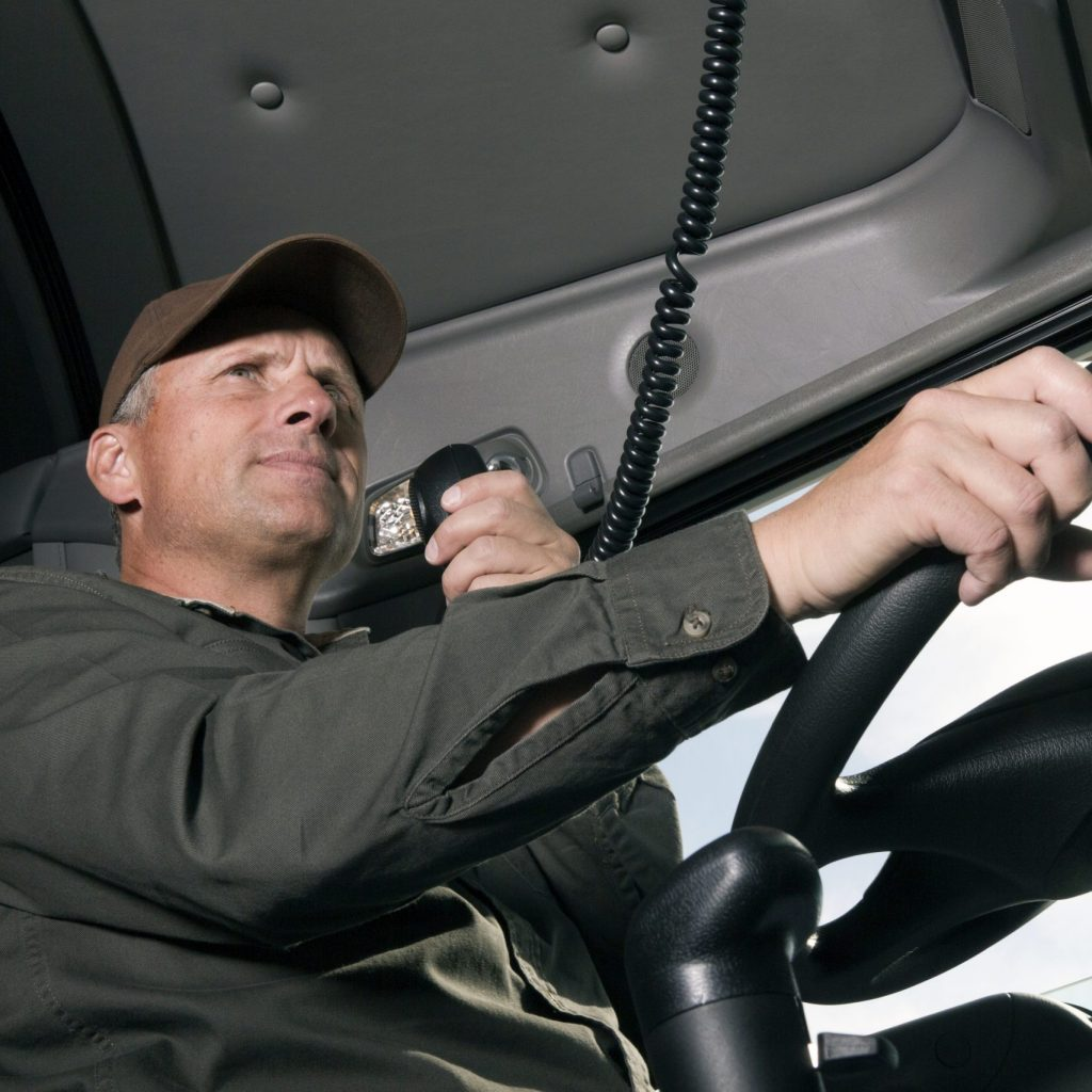 A truck driver uses his CB radio.
