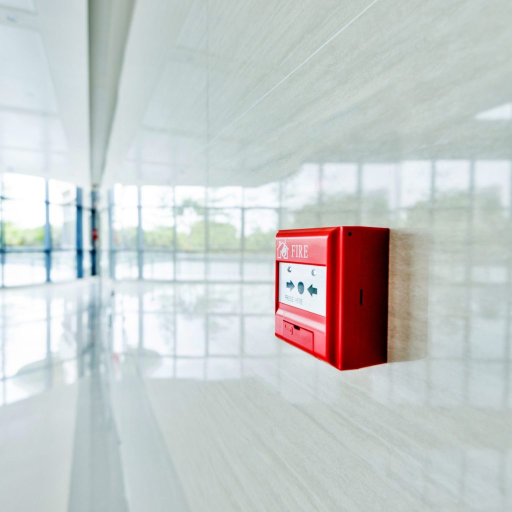 Red fire alarm on white wall.