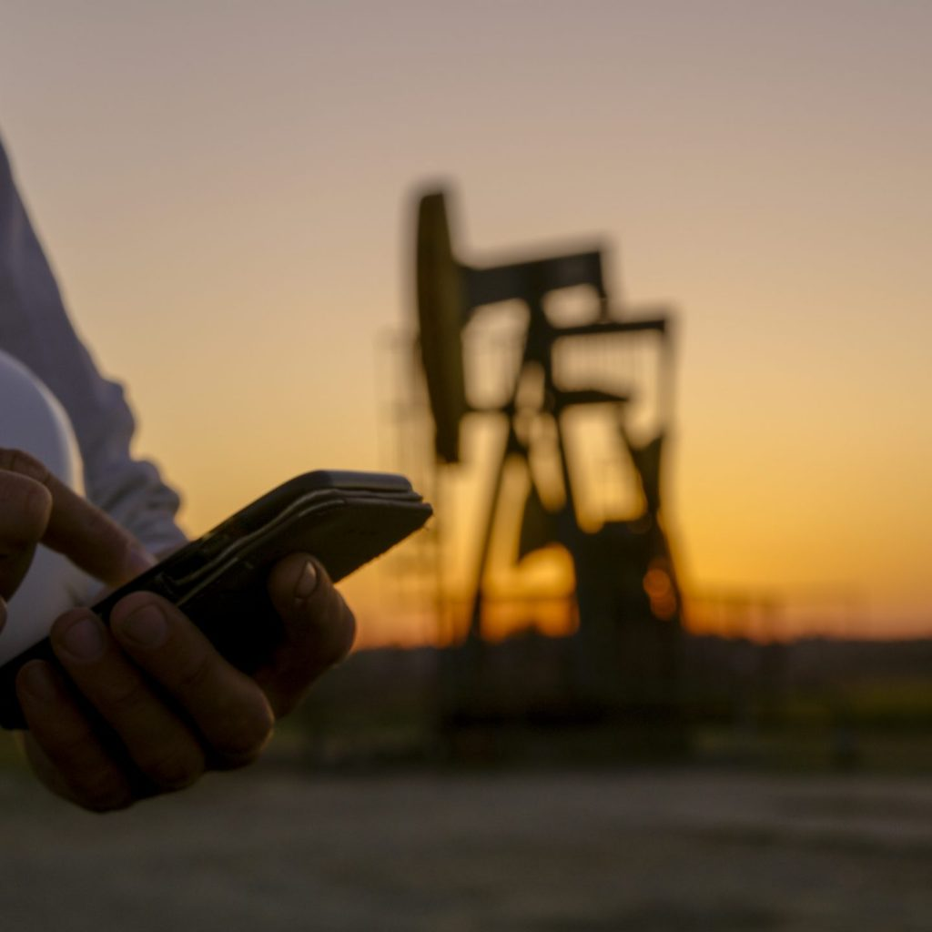 Close up of smart phone against pumpjack