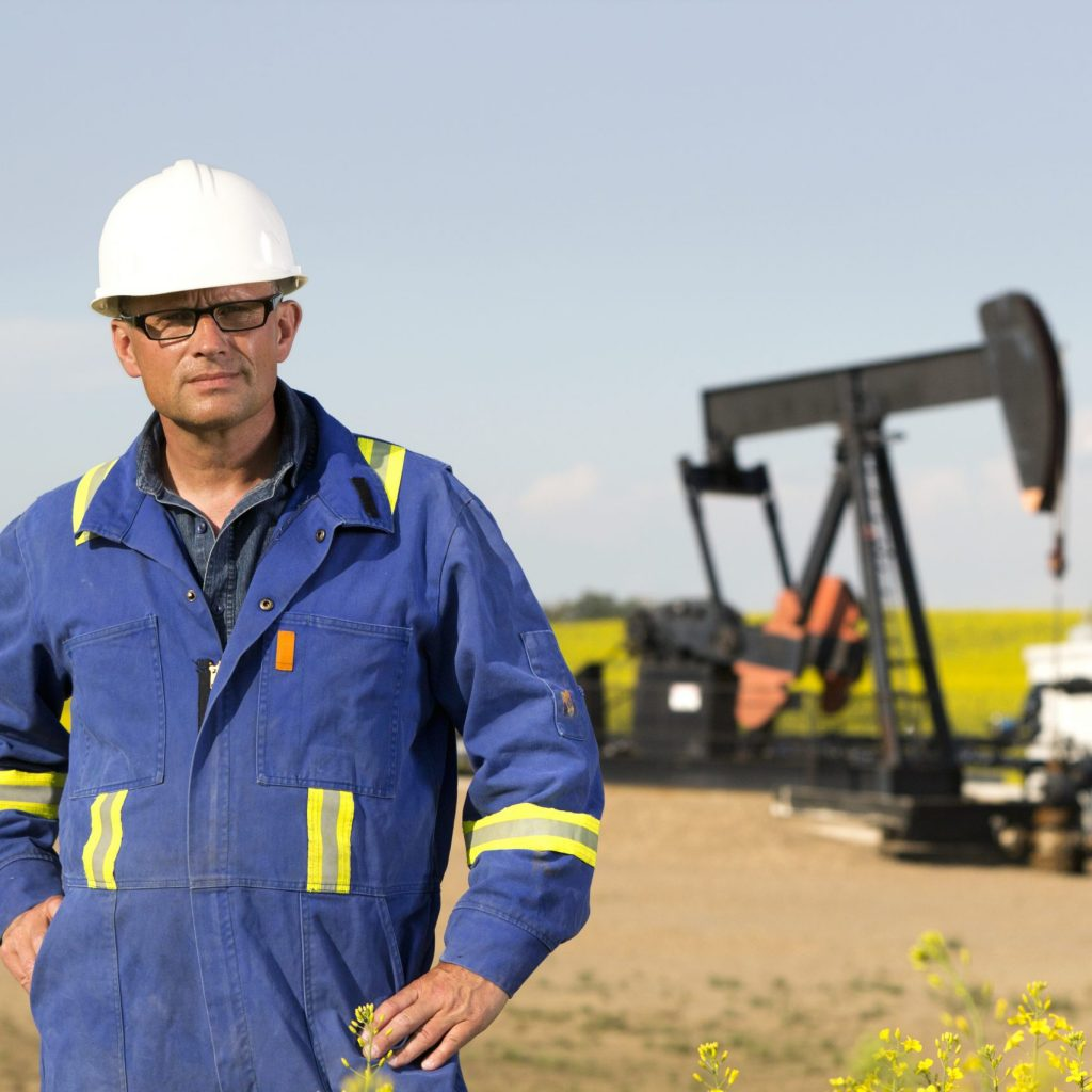 A royalty free image from the oil and gas industry of an engineer standing in front of oil equipment.